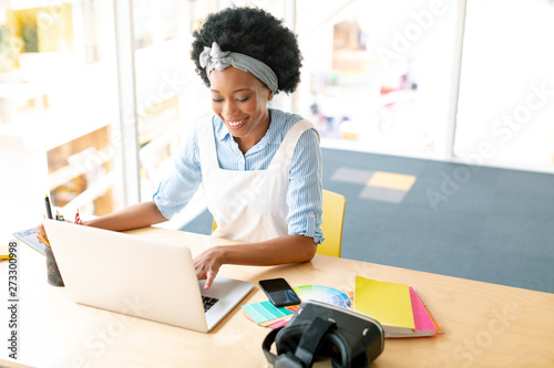 Female graphic designer using graphic tablet and laptop at desk Canvas-taulu