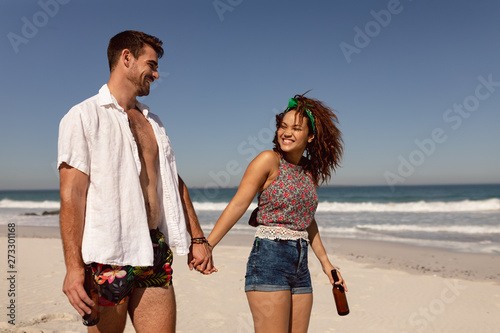 Young couple with beer bottle walking on beach in the sunshine