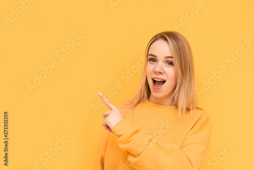 Portrait of surprised sweet lady showing thumb to the side