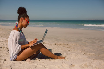 Woman sitting on sand and using laptop at beach in the sunshine