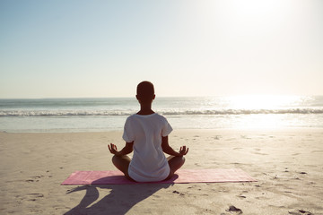 Woman performing yoga on the beach