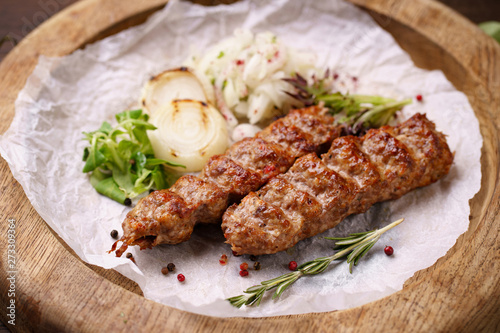 Traditional Adana kebab on wooden plate with marinated onion garnishing and spicy aromatic herbs Wallpaper Mural