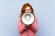 Redhead woman in suit over isolated blue wall shouting through a megaphone