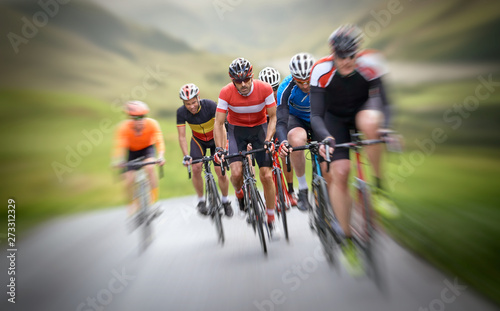 Cyclists out racing along country lanes in the mountains in the United Kingdom.