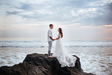 Elegant Gorgeous Bride And Groom Walking On Ocean Beach During Sunset Time. Romantic Walk Newlyweds On Tropical Island. Concept Marriage, Just Married