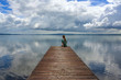 A woman is sitting alone on a wooden walkway at the Lago di Bracciano in Italy
