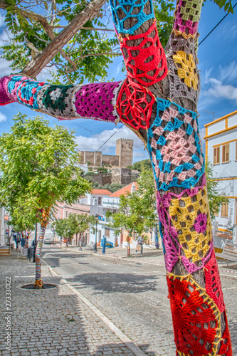 Trees decorated with colorful crochet patchwork on a holiday in the town of Mertola, a very beautiful city in the Portuguese Alentejo area Fototapete