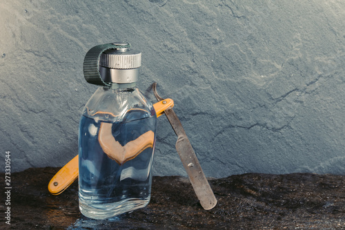 Photo Clear blue aftershave bottle with old razor on wet stone texture