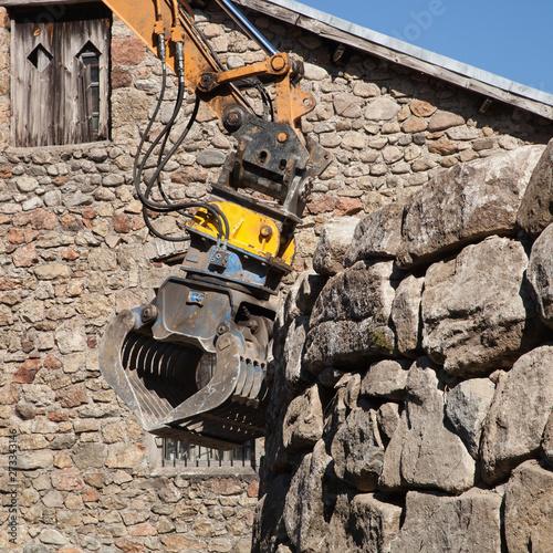 Une pelle mécanique ajuste les pierres d'un enrochement Wallpaper Mural