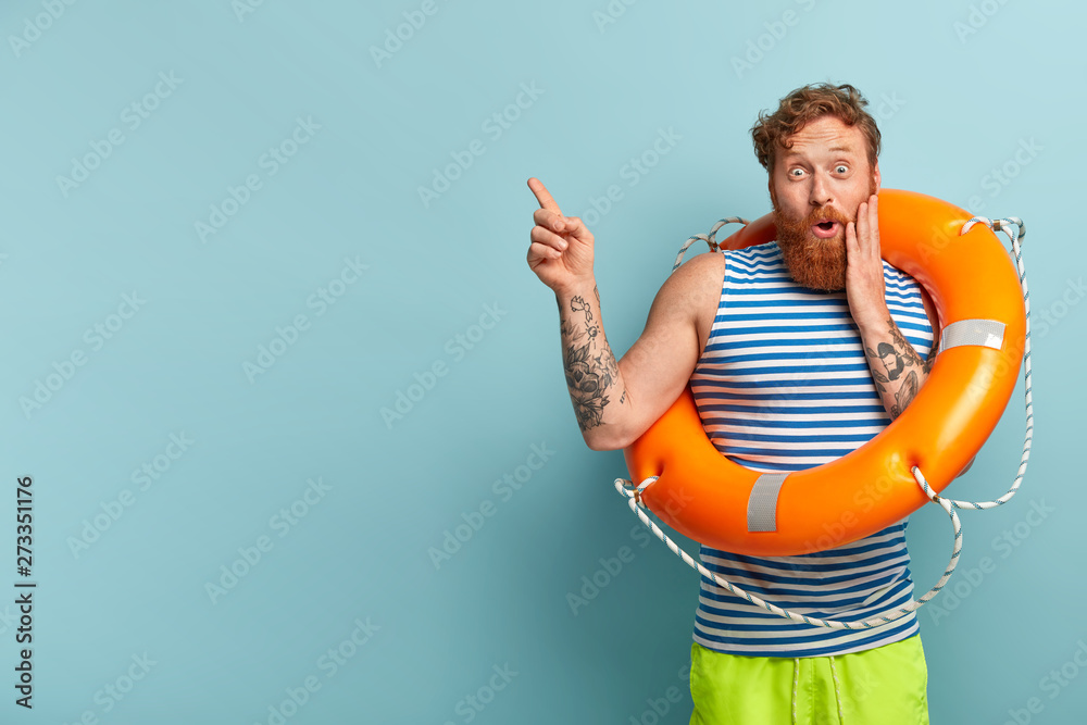 Fototapety, obrazy: Safe sinking concept. Astonished red haired man holds orange lifebuoy, maintains safety, wears sailor vest, has happy surprised expression, isolated on blue background with free space for information