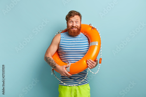 Fotografie, Obraz  Happy carefree male with life preserver, has glad reaction, grins at camera, stands in casual clothes, isolated over blue backgound