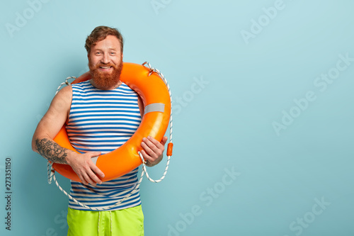 Canvas Print Positive bearded red haired guy wears striped sailor vest, carries orange lifebuoy, stands over blue background with blank copy space for your advertising content