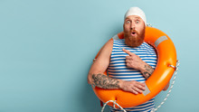 Studio Shot Of Stupefied Lifeguard Points Away On Left Side, Keeps Mouth Opened From Amazement, Dressed In Casual Swimwear, Poses With Lifebuoy, Isolated On Blue Background, Free Space For Your Advert