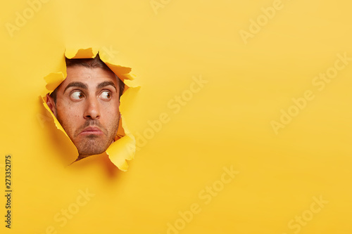 Fotomural Face of surprised scared young man gazes through yellow paper hole aside, sees s