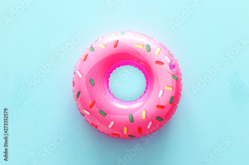 Cuadros en Lienzo Inflatable donut ring over blue wooden background
