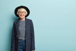 canvas print picture - Active joyful stylish female teacher retires, wears hat and formal jacket, glad receiving congratulation from colleagues, has charming smile on face, isolated on blue wall, copy space area for advert