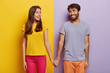 canvas print picture - Romantic couple in love have date, hold hands, look positively at each other, feel support, walk together. Positive man poses over purple background, woman on yellow. Contrast. Relationship concept