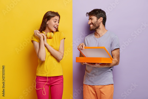 Happy young male model opens box, makes surprise for girlfriend on birthday, shows something in package, isolated over purple background. Glad lovely woman with headphones on neck, receives gift