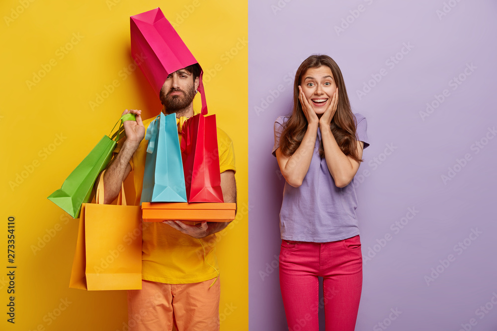 Fototapeta Sad man overloaded with shopping bags, has wife shopaholic, spend free time during weekend on buying new clothes, pose indoor. Positive woman rejoices successful purchases, spends money unwisely