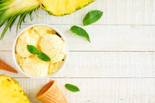 Bowl Of Pineapple Coconut Ice Cream. Above View Side Border Over A White Wood Background. Copy Space.