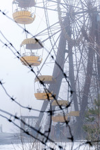Selective Focus Of Metal Barbed Wire In Front Of Ferris Wheel Attraction In Foggy Winter Abandoned Amusement Park Overgrown With Trees In Pripyt, Chernobyl Zone Of Alienation
