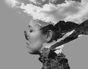 Black and white double exposure combined photographs with the Asian young woman wearing retro sunglasses and mountains.