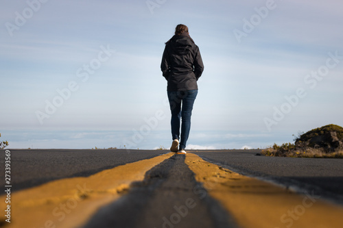 Fotografie, Tablou  Woman walking on the line down the street above the clouds