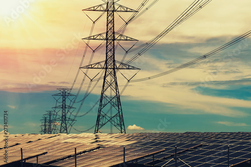 Fotografia Solar panels with electricity pylon and sunset