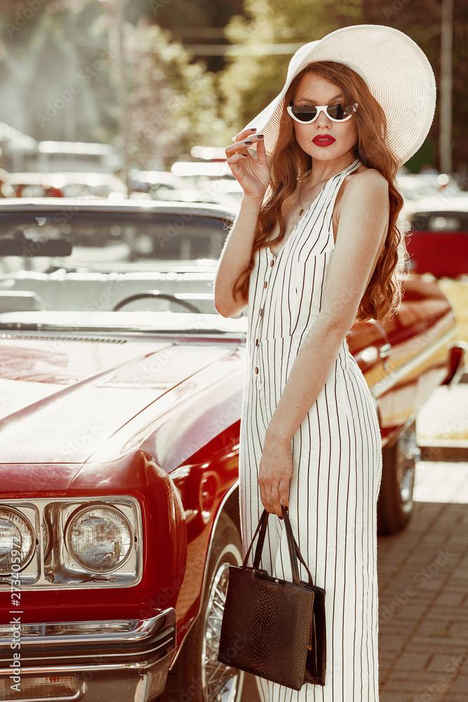 Fototapeta Street fashion portrait of young elegant luxury woman wearing wide brimmed hat, striped linen jumpsuit, sunglasses, holding classic black handbag