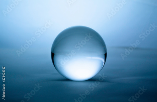 Photo Crystal glass ball sphere transparent on blue gradient background