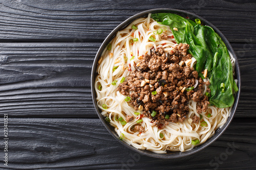 recipe for dan dan noodles with minced meat and greens closeup in a plate Fototapeta