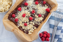 Closeup Of Chocolate Cake With Raspberry And Streusel On A Table