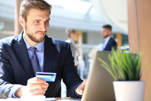 Smiling Man Sitting In Office And Pays By Credit Card With His Laptop.
