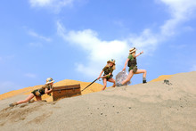 Young Twin Sisters And An Adult Girl Dress Up As Explorers.  They Pretend To Be Hauling An Old Luggage Chest Up A Sand  Dune Hill. The Girls Are Dressed In Khaki Safari Clothes And  Wear Jungle Hats.