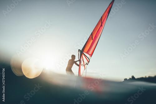 Windsurfer catching the wind on board  Low angle splashing