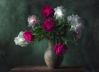 Classic still life with beautiful white and purple peony flowers bouquet in ancient jug. Art photography.