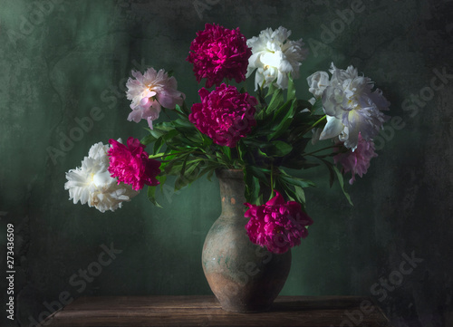 Fototapeta Classic still life with beautiful white and purple peony flowers bouquet in ancient jug. Art photography. obraz