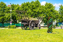 Rustic Cart. Vintage Wooden Hay Wagon. Monument In A Modern Village.