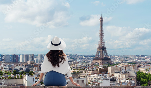 Poster Tour Eiffel Traveling in Europe, Young woman in white hat looking at Eiffel tower, famous landmark and travel destination in Paris, France in summer