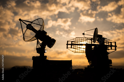Silhouettes of satellite dishes or radio antennas against sunset sky Canvas Print