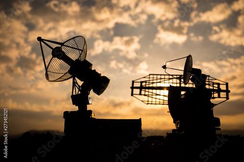Cuadros en Lienzo  Silhouettes of satellite dishes or radio antennas against sunset sky