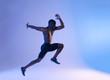 Muscular African-American shirtless man leaping blue light.
