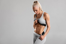 Fitness Woman Showing Abs And Flat Belly, Isolated On Gray Background. Beautiful Athletic Girl, Shaped Abdominal