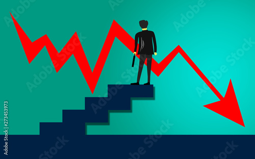 Businessman standing in front of a downward line graph Fototapeta