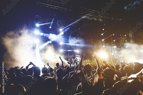 Young people dancing and having fun in summer festival party outdoor - Crowd with hands up celebrating concert event - Soft focus on center hand with yellow background flare - Fun and youth concept - 273454989
