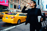 Fototapeta Nowy Jork - Serious woman in elegant formal wear waiting for taxi cab near traffic on road hurry up for important business meeting with company partners, attractive female trader with takeaway cup outdoors