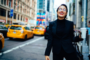 Cheerful financial expert with coffee to go laughing on modern street while waiting for taxi cab near road with traffic on Manhattan, happy excited businesswoman in optical spectacles feeling good