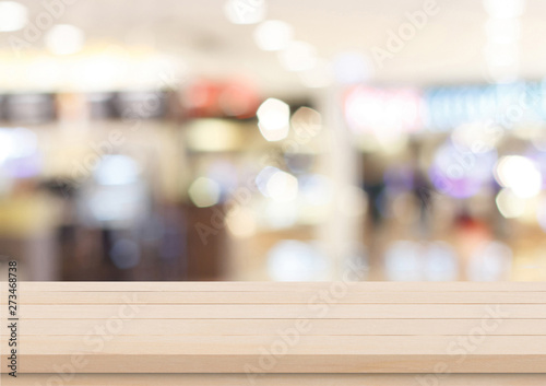 Fotografiet  Empty brown wood table top on blur abstract background from inside shopping mall, Used for display or montage your products