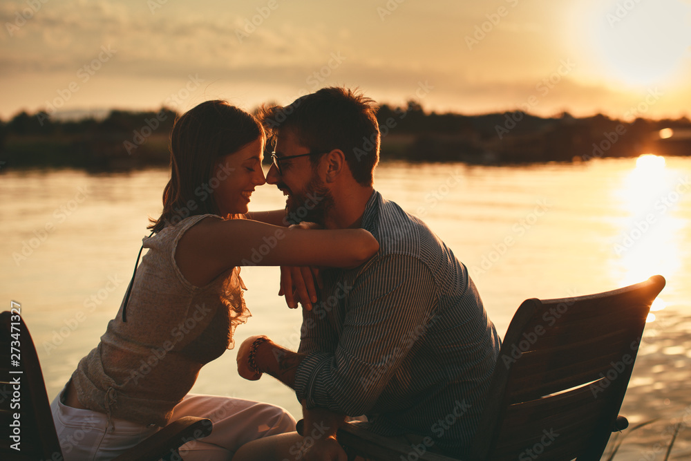 Fototapeta Young couple in love flirting by the river at sunset
