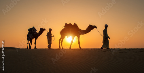 Rajasthan travel background - Two indian cameleers (camel drivers) with camels silhouettes in dunes of Thar desert on sunset Fototapet